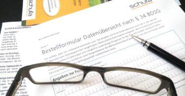 Antrag auf Schufa Auskunft auf Schreibtisch mit Brille und Stift
