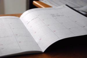Aufgeschlagener Kalender auf Tisch
