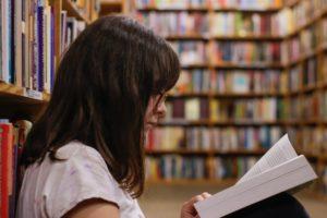 BAföG geförderte Studentin liest ein Buch auf dem Boden der Bibliothek sitzend