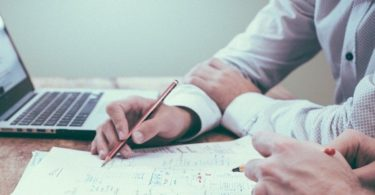 Berater einer Schuldnerberatung zeigt Notizen auf Zettel und Laptop