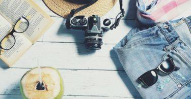 Buch Kamera Sonnenbrille liegen bereit nach Reise stornieren