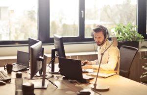 Bürokaufmann mit Berufsunfähigkeitsversicherung am Computer arbeitend