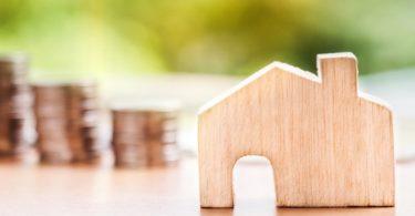 Drei Stapel Kleingeld hinter Miniaturholzhaus vor grünem Hintergrund für Baufinanzierung