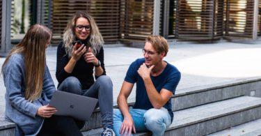 Drei Studenten sitzen mit Laptop auf Treppe und unterhalten sich über BAföG