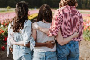 Drei junge Frauen mit Gemeinschaftskonto stehen Arm in Arm