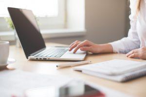Frau arbeitet an online Wertpapierdepot über Laptop und Notizbuch auf Holztisch