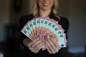 Frau hält Zehn Euro Scheine von Kredit ohne Schufa
