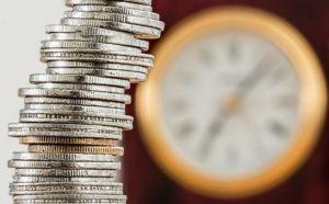 Gestapelte Münzen vor Uhr Wartezeit Erwerbsminderungsrente
