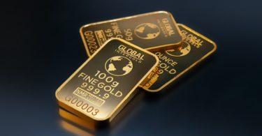 Gold kaufen in Form von Barren auf dunklem Hintergrund