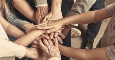 Viele Hände aufeinander gestapelt als Zeichen der Unterstützung für Privatkredit