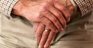 Hände eines Herren mit Pflegeversicherung die sich auf Gehstock aufstützen