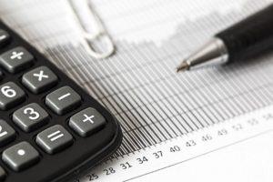 Kalkulation der Betraege fuer Private Krankenversicherung mit Taschenrechner und Stift