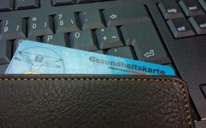 Krankenkassen Karte in Geldbeutel auf Tastatur