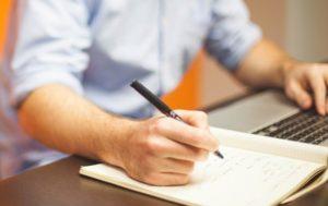 Mann macht Notizen und nutzt Kreditrechner auf Laptop