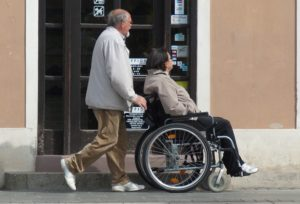 Angehöriger schiebt Frau in Rollstuhl mit gesetzlicher Pflegeversicherung