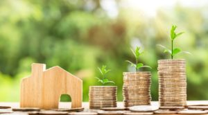 Mini Holzhaus und gestapeltes Kleingeld vor grünem Hintergrund für Bausparvertrag