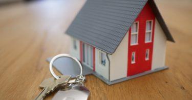 Miniaturhaus und Schlüssel symbolisch für Plan auf Erbbaugrundstück zu bauen