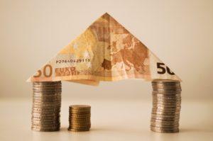 Münzen und Geldschein zu Haus mit Nebenkostenabrechnung gestapelt