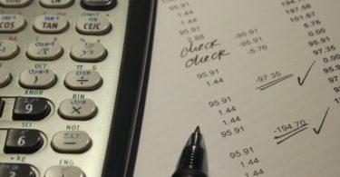 NV-Bescheinigung mit Rechnungen Taschenrechner und Stift