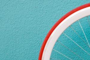 Nahaufnahme Rad eines E-Bikes mit Versicherung vor blauer Wand