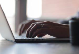 Person schreibt an Laptop Kredit umschulden