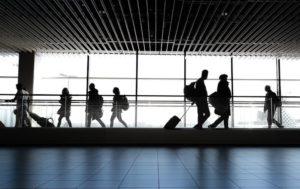 Reisende mit Fluggastrechten gehen Flughafen mit Koffern entlang