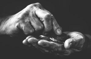 Rentner zählt Münzen für gesetzliche Pflegeversicherung