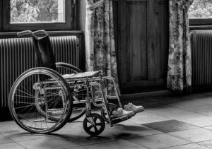 Rollstuhl einer Person mit Erwerbsminderungsrente vor Fenstern