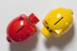 Rotes und gelbes Sparschwein für Beiträge Pflegezusatzversicherung
