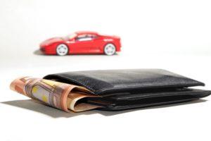Rotes Spielzeugauto hinter 50-Euro-Scheinen in Geldbeutel für Autokredit