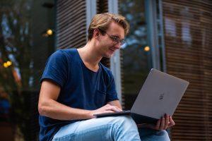 Student informiert sich an Laptop über Kredit mit Bürgen
