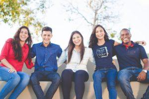 Fünf Studenten mit Studienkredit Arm in Arm