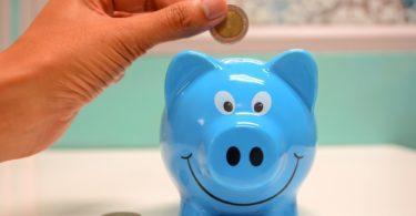Taschengeld nach Taschengeldtabelle wird in blaues Sparschwein geworfen