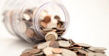 Umgefallener Behälter mit herausfallenden Tagesgeld Münzen
