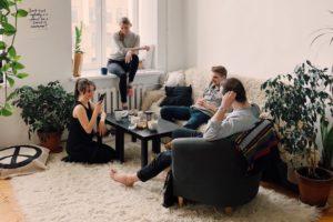 Vier junge Erwachsene mit Bausparvertrag sitzen auf Sofa in Wohnzimmer
