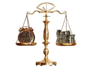 Waage mit Geld und Wecker für Zeitpunkt von Mahngebühren