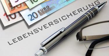 Lebensversicherung Geld Stift und Brille auf Tisch